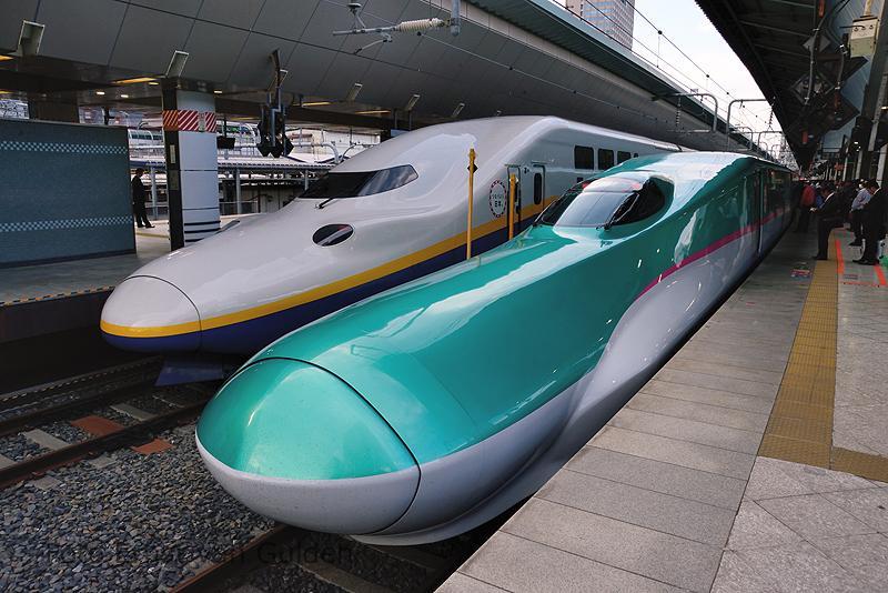 """Aan de andere zijde van het Centraal Station is de terminal voor de Shinkansen. Zowel de lijn(en) uit het Noorden (Nagano, Tôhoku en Jôetsu Shinkansen) als het zuiden (Tôkaidô Shinkansen) eindigen hier naast elkaar met een kopstation.Op de foto zien we twee typen naast elkaar. Links staat een E4-series (Shinkansen """"MAX"""", dubbeldeks), welke in dienst kwam vanaf 1997 en rechts een E5-series, welke in dienst kwam vanaf 2011. Beide series rijden normaal gesproken op de Tôhoku en Jôetsu Shinkansen."""