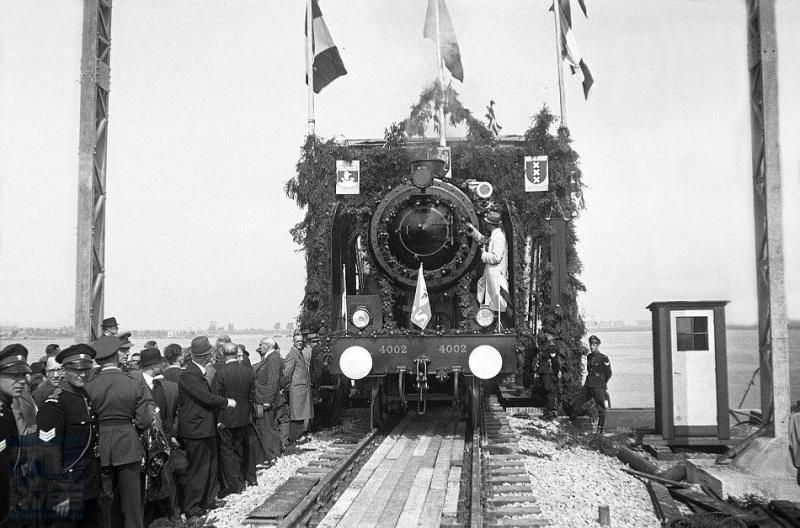 Groot feest: de Moerdijkbrug is hersteld! Op deze foto gaat een directietrein als eerste het Hollands Diep over en bereikt over enkele minuten Noord-Brabant. De trein wordt getrokken door stoomlocomotief 4002. Dit is een machine uit de serie 4001-4015 die na de oorlog uit Zweden het NS-locomotievenpark kwam versterken. Ze zijn gebouwd door Nohab in Trollhättan; bij de NS zijn het de enige 2C-locs met drie cilinders. (foto J.J.Overwater; 24-8-1946)