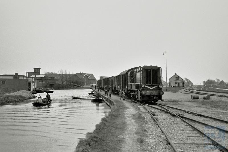 """We blijven nog even in Noord-Holland.We zien loc 534 met een buurtgoederentrein in Noord-Scharwoude; rechts het spoor naar Heerhugowaard. Deze situatie heeft tot 1973 bestaan. Per boot werd witte kool aangevoerd om verder per trein te worden getransporteerd.In deze streek werd veel groente per boot aangevoerd, zoals nog te zien is in het museum """"de Broeker Veiling"""" te Broek-op-Langendijk."""