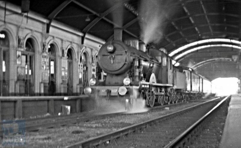 Een dag later fotografeerde Hesselink ongeveer op dezelfde plek een andere trein, nu duidelijk eentje in het personenverkeer. Een van de fraaiste locomotieven van de NS staat er voor: de 2B 2117 uit de serie 2101-2135. Bij de HSM hadden deze locs de nummers 501-535. De door Schwartzkopff in Berlijn vanaf 1914 gebouwde machines waren het antwoord van de HSM op de zware locs -de latere serie NS 3700- die de SS in dienst hadden gesteld. Ir. W.Hupkes heeft, met het Pruisische type S6 als voorbeeld, deze sneltreinlocomotief ontworpen met de maximaal toegestane asbelasting van 17 ton/as en met drijfwielen van 210 cm in doorsnee. Zijn alle passagiers al in- of uitgestapt? Geen mens te zien! 24 februari 1935 (NVBS-fotonummer 170.218).