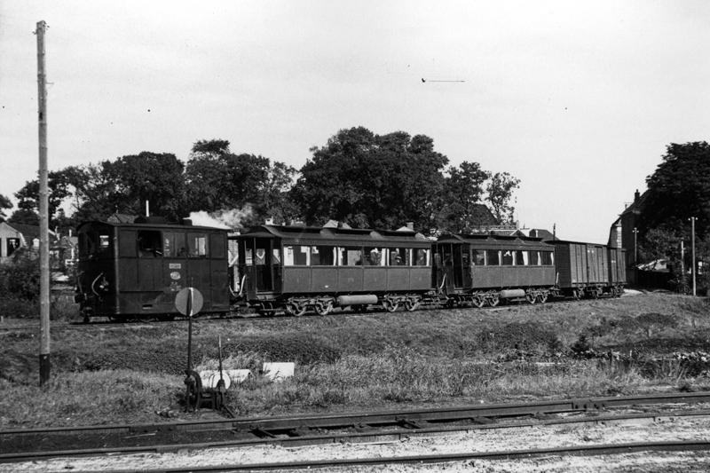 Op 3 oktober 1936 nadert NTM locomotief 36 met personenrijtuigen BC 6 en BC 5 en met enkele goederenwagens het station Heerenveen. De tram komt uit de richting Drachten, via toen de nieuw aangelegde omleidingsroute buiten de bebouwde kom van Heerenveen om. De foto werd gemaakt door L.J. Biezeveld.