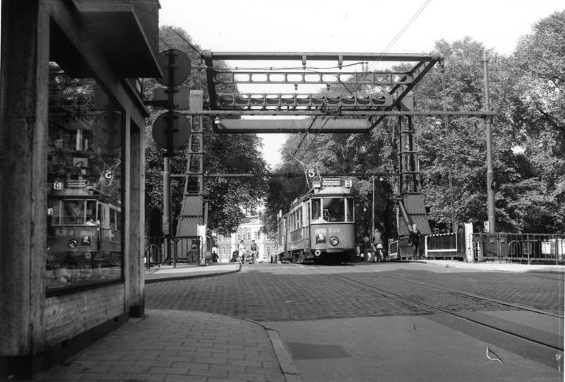 Het afscheid van de Utrechtenaren in Amsterdam kondigde zich in het jaar 1960 al duidelijk aan. Ook de oude Weesperstraat, of liever gezegd wat daar nog van over was, zou al spoedig moeten wijken voor de aanleg van een brede autoweg. Op deze foto van Ab van Donselaar van 18 september 1960 is daarvan nog weinig te zien. Wat een rust gaat er uit van dit tafereeltje rond de vroegere brug over de Nieuwe Herengracht, met op de achtergrond het nog ongeschonden Jonas Daniël Meijerplein. Het tramstel op de brug bestaat uit motorwagen 308 (eens nummer 68 in de Domstad) en bijwagen 777. Een jaar later zou de tram hier voor het laatst rijden. Ook de nieuwe brug op deze plaats was aanvankelijk van tramspoor voorzien. Niettemin zou de tram hier niet meer terugkeren.
