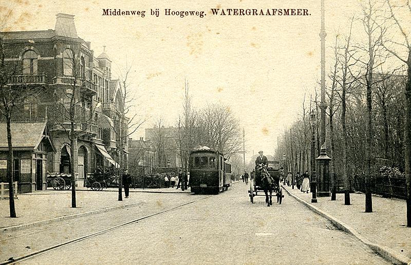 Rond 1915 staat de Gooische Stoomtram aan de halte nabij het Hoofdkantoor van de GS aan de Middenweg in Amsterdam. Achter dit gebouw, dat overigens nog steeds bestaat en inmiddels in oude luister is hersteld, bevond zich de remise en de werkplaats. Tegenwoordig rijden hier de Combino′s van lijn 9. Verzameling Ab van Donselaar.