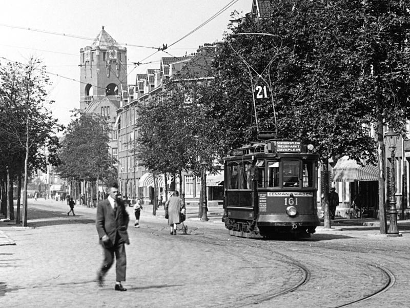 """Ook deze opname van de schaars gefotografeerde Amsterdamse tramlijn 21 komt uit de verzameling van Jos. Het is de originele foto van een ansichtkaart, destijds uitgegeven door Arthur Klitsch. Ogenschijnlijk berijdt EMW 161 op het Javaplein """"verkeerd spoor"""", om het in spoortermen te zeggen. Om linksaf te kunnen buigen naar de standplaats in de Molukkenstraat, met het kringspoor Madurastraat, moest hij heel kort via een overloopwissel het spoor van de tegenrichting gebruiken. Vanaf 1932 zou nummer 161 niet langer als zelfstandige tram dienst doen, maar onderdeel uitmaken van de eerste harmonicatram in de hoofdstad (161/162), zoals deze vroege voorloper van de gelede tram van 1957 destijds heette."""