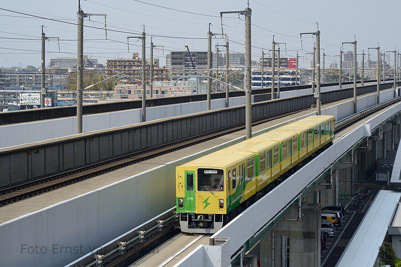 De New Shuttle is een automated guideway transit (AGT) systeem (met bestuurder) op rubber banden. De 12,7 km lange lijn loopt in het noorden van Tokio tussen de stations Ōmiya en Uchijuku. En wordt geëxploiteerd door de Saitama New Urban Transit Co., Ltd Hier zien we een series 1010 het station Tetsudō-Hakubutsukan (Spoorwegmuseum) naderen. De lijn loopt voor een deel (links) naast de Jōetsu Shinkansen richting Noord-Japan.De foto is genomen vanaf het dak van het spoorwegmuseum, dat (schuin)onder de beide spoorlijnen ligt.