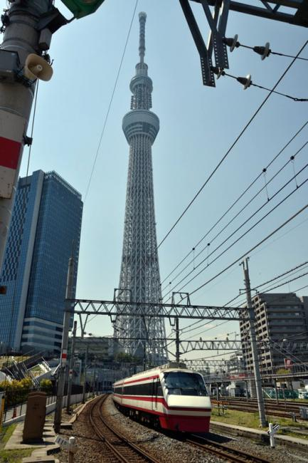Een trein van de Tobu Railway passeert op 13 april 2013 de 634 meter hoge skytree. De sneltreinreeks 200 series Ryômô limited express, die ingezet wordt op de Tobu Skytree Line, is hier op weg naar Kuzû.