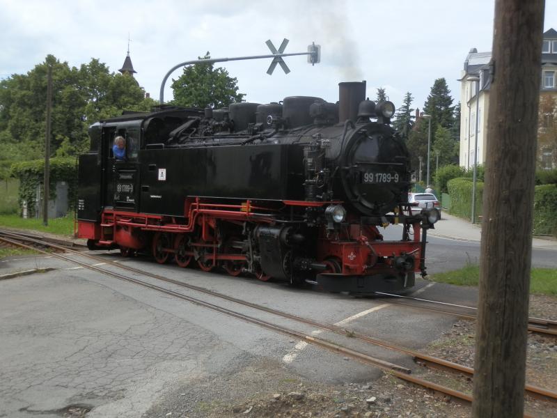 """De ruim 16 kilometer lange spoorlijn loopt eerst direct langs de openbare weg in Radebeul. Onderweg wordt de Dresdense tramlijn 4 gekruist. Eenmaal uit Radebeul loopt de lijn door een licht glooiend landschap. Hoogtepunt is de oversteek van een meer over een 210 meter lange dam. De helft van de treinen eindigt in Moritzburg waar op een 20 minuten lopen van het station een prachtig sprookjesachtig slot staat. Op dit station Moritzburg rangeert de 99 1789 om zijn trein heen. De 99 1789 is van het type """"VII K Neubau"""". De Saksische smalspoorlocomotieven werden aangeduid met de K van de Kleinspur en een typenummer in Romeinse cijfers. De """"VII K Neubau"""" waren de laatste, in de jaren '50 gebouwde locomotieven en waren afgeleid van de vooroorlogse VII K die daarna natuurlijk """"VII K Altbau"""" werden genoemd. Ik heb tijdens mijn vakantie alleen VII K's gezien maar oudere types zijn her en der nog aanwezig. Zeker voor Traditionszüge worden ook nog IV K's ingezet, de beroemde Meyerlocomotieven. Er werden tussen 1891 en 1922 maar liefst 96 stuks van gebouwd. De IV K heeft twee twee-assige draaistellen. De assen in het achterste draaistel worden aangedreven door hogedrukcilinders, de assen in het voorste draaistel door lagedrukcilinders."""