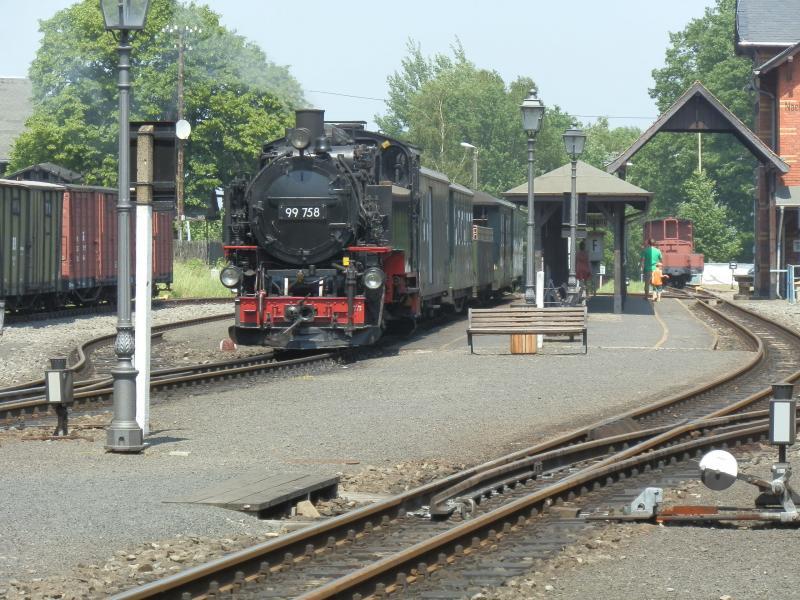 """Bij het drielandenpunt met Tsjechië en Polen vinden we de smalspoorlijn van Zittau naar Kurort Oybin en Kurort Jonsdorf. De lijn splitst in het bijzonder sfeervolle station Bertsdorf, waar deze foto is genomen. De 99 758 is een VII K Altbau uit 1933. Meestal wordt rechtstreeks gereden naar Kurort Oybin en staat in Bertsdorf de aansluitende trein naar Kurort Jonsdorf gereed. Er kan meerdere malen per dag van een """"Parallelausfahrt"""" worden genoten, zij het dat het naast elkaar rijden slechts enkele tientallen meters betreft. De Zittauer Schmalspurbahnen worden geëxploiteerd door de SOEG (Sächsisch-Oberlausitzer Eisenbahngesellschaft)."""