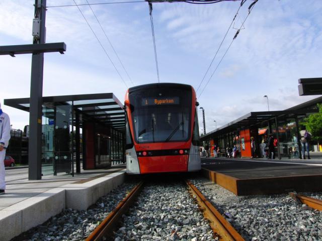 De eerste tramlijn van de Bergen Bybanen sinds lange tijd is net nieuw (geopend op 22 juni 2010). We rijden de hele 9,8 km lange lijn met max. 70 km/u heen en terug langs lachwekkende haltes, zoals Sletten en Slettenbakken. Daarbij reizen we met een chipkaart waarmee we eerst moeten innsjekken.Let op het bord links op de foto, dat het andere verkeer moet waarschuwen voor de komst van dit nieuwe… railvoertuig.De mooie moderne voertuigen (al met enkele vierkante wielen) zijn normaalsporig, zodat ze gedeeltelijk over het hoofdspoornet hierheen hebben kunnen komen.Foto: Theo Gramser Periode: juli 2010