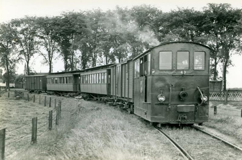 De paardentram was niet opgewassen tegen de enorme concurrentie van de autobussen. Daarom wilde de NTM de lijn al midden jaren twintig sluiten. De Provincie Friesland verbood dit. Uiteindelijk stemde ook de gemeente Dantumadeel in met de komst van stoomtrams en motorwagens. De lijn werd verzwaard en op 15 mei 1926 feestelijk in gebruik genomen. Hier een stoomtram met loc 40 in augustus 1936 te Veenwouden met een tram naar Dokkum. Foto: J.J.B. Vellekoop.