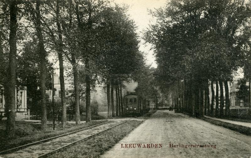 Na de boog liep de lijn langs de Harlingerstraatweg, zoals hier te zien is. De tram rijdt naar Marssum. De lijn Leeuwarden - St. Jacobiparochie liep voor het overgrote deel in de berm van de weg. Slechts enkele kleine stukken lagen op eigen baan.