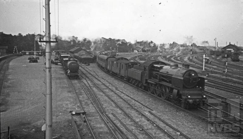 Aan de oostkant van het emplacement zien wij loc 3913 met internationale trein 111 vertrekken uit Amersfoort richting Duitsland. Het aantal personenrijtuigen was in die tijd, 6 augustus 1935, beduidend lager dan wat we nu  in het internationale treinverkeer gewend zijn. Helemaal rechts op de foto kunt u het locomotievendepot nog zien.