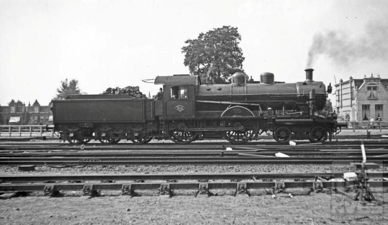 Tussen de voorlopers van de NS is er altijd sprake geweest van concurrentie. Vooral tussen de twee grote: HSM en SS.  De serie  2B-locomotieven 501-535 was in 1914 het antwoord van de HSM op de een paar jaar eerder bij de SS in dienst gestelde 2C-machines, de latere 3700-en bij de NS. De HSM-locs waren wel wat lichter, maar door hun constructie met binnenliggende cilinders en enorme drijfwielen -2100mm in doorsnee-, uitstekend in staat snelle prestaties te leveren. Bij de NS kreeg de serie de nummers 2101-2135.  Had de keuze van deze nummering soms iets te maken met eerdergenoemde wieldiameter? Op de foto staat de 2115 onder stoom op het emplacement, maar wat zij ging doen kunnen we van de foto niet aflezen. Hesselink maakte deze plaat op dezelfde dag als de vorige: 10 augustus 1935.