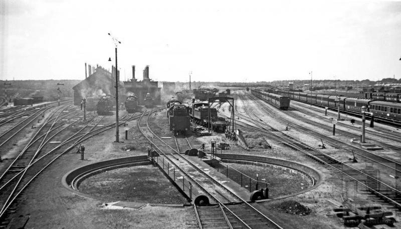 Deze foto geeft een goed overzicht van het gigantische emplacement van station Amersfoort, zoals het er op 5 juli 1936 bij stond. Vooraan de draaischijf en meer naar achteren locomotieven onder stoom voor de loods. Rechts rijen met treeplankrijtuigen.