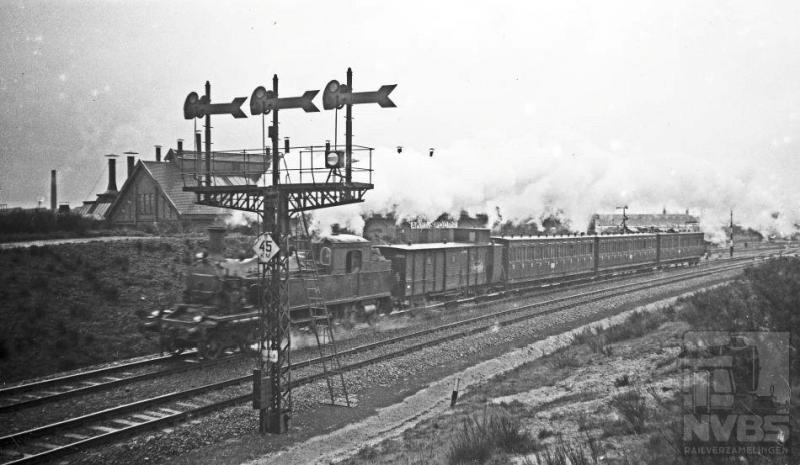 Aan de ene kant een drievoudig vertakkingsein, het inrijsein voor Amersfoort met bordje voor de toegestane snelheid en aan de andere kant een uit Amersfoort vertrokken reizigerstrein. De foto is niet helemaal scherp zodat het locnummer niet is te onderscheiden; het is er in ieder geval een uit de serie NS 5806-5812.  Deze tenderlocs, gebouwd door Werkspoor, kwamen in  1915 in dienst bij de HSM.  3 mei 1936.
