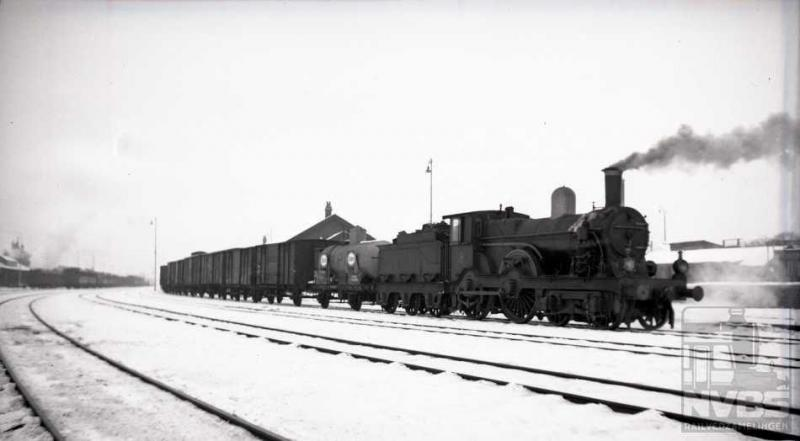 """""""Vroeger hadden we tenminste nog echte winters"""": op Tweede Kerstdag 1938 zien wij een 1700-er met een goederentrein het emplacement van Amersfoort verlaten voor een tocht in een witte en stille wereld. Het betreft hier een locomotief uit de grootste serie van de NS, namelijk NS 1700-1835 (135 stuks  ). Er zijn verschillende subseries te onderscheiden, de meeste afkomstig uit Engeland terwijl een tiental machines door Werkspoor zijn gebouwd. Aan de grote drijfwielen is te zien dat zij -aan het eind van de 19e eeuw- ontworpen zijn om sneltreinen te trekken. In de dertiger jaren echter waren er voor dit doel al sterkere locs bij de NS aanwezig waardoor de 1700-en degradeerden tot trekkracht voor lokaal- en goederentreinen."""