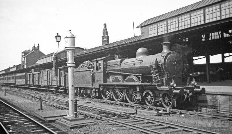 Op deze foto staat locomotief NS 3505 met een reizigerstrein langs het perron. Aan de andere kant zien we nog net een rijtuig van een internationale of sneltrein. De waterkolom op de voorgrond mag er ook zijn, met dat grappige lantaarntje bovenop. Deze 2C-locomotief, afkomstig van een kleine serie van acht stuks, kwam in 1908 in dienst bij de Noord-Brabantsch-Duitsche Spoorwegmaatschappij (NBDS), de kleinste die Nederland heeft gekend. Op ons grondgebied reden deze locs van Boxtel via Veghel en kruispunt Beugen naar de grens met Duitsland, waar het verder ging naar Gogh en Berlijn. Maar dan met een Duitse loc ervoor natuurlijk. Het is 12 augustus 1935.