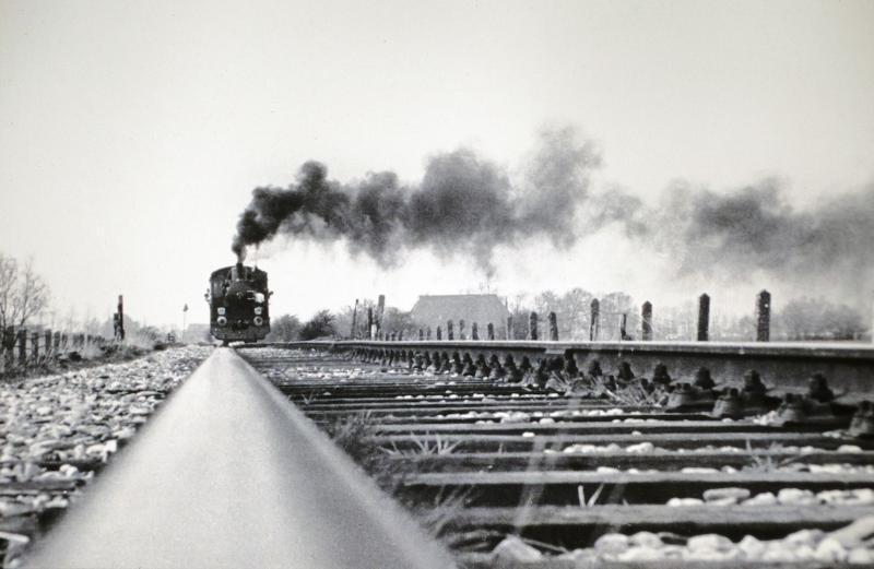 Na veel strijd knapte de NS de lijn Leeuwarden - Stiens op in het kader van een werkgelegenheidsproject en liet de ZPC een (toen) hypermodern sorteercentrum met spooraansluiting bouwen in Stiens. Om dit te vieren pendelde de eerste week in mei 1976 locomotief 21 van de Stoomtram Hoorn - Medemblik tussen Leeuwarden en Stiens, zoals hier te zien is nabij het Vliegveld Leeuwarden op 1 mei 1976. Foto: Hans Elzinga