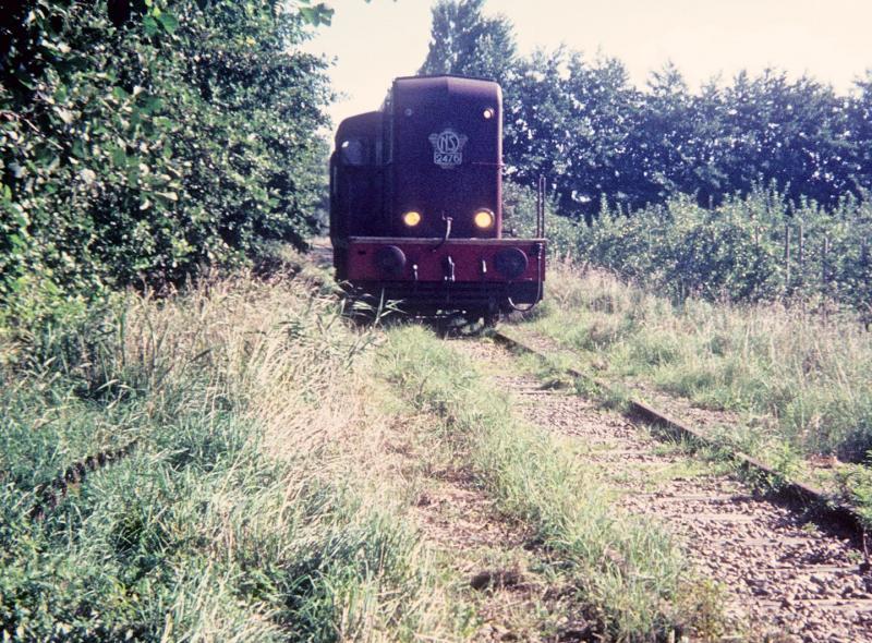 Stiens - Minnertsga was de eerste tak van de NFLS die werd gesloten. De reden: er was nauwelijks onderhoud gepleegd (en dat is te zien op de foto) en de lijn was te slecht om te berijden. Dus reed loc 2476 op 24 september 1971 de laatste trein naar Minnertsga, hier tussen St. Anna Parochie en St. Jacobi Parochie. Foto: Lieuwe van der Leij.
