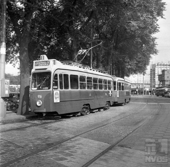 """De meeste tramlijnen deden natuurlijk het Amsterdamse Centraal Station aan. De niet meer bestaande lijn 27 op deze foto uit 1968 toont een drieassig tramstel van een serie die het Gemeentevervoerbedrijf kort na de oorlog bij Werkspoor had besteld. Dit in tegenstelling tot Rotterdam en Den Haag die allebei ongeveer tegelijkertijd bestellingen deden voor vierassers. Motorwagen 916 heeft een zogenaamde """"bloedneus"""" welke op een zwartwit foto moeilijk te zien is. Deze bloedneus gaf aan dat op de motorwagen geen conducteur meer dienst deed.Foto: J.W.A.Jekel (1129.825A)"""