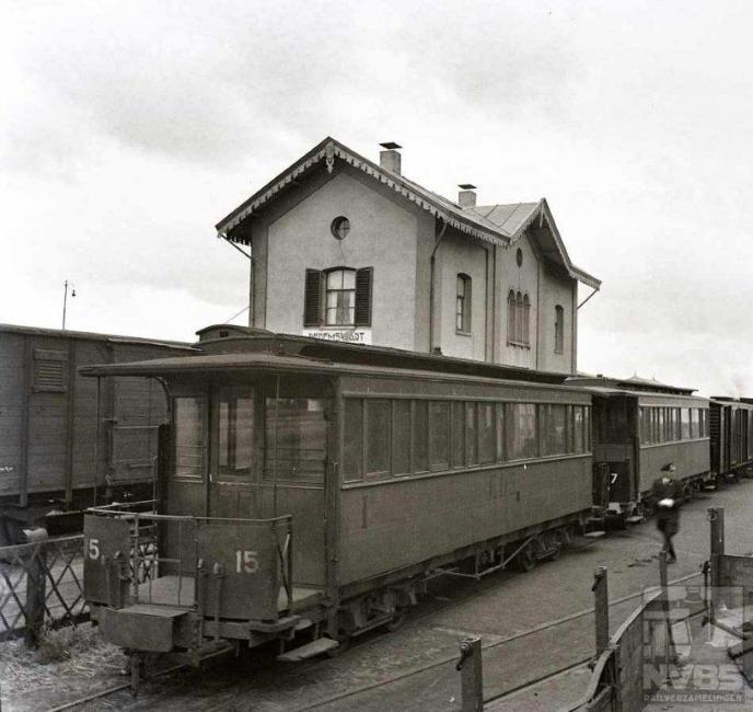 Op deze foto uit de oorlogstijd, 23 mei 1944, zien we een tram van de Eerste Drentsche Stoomtramweg Maatschappij (EDS) met een reizigerstram aankomen bij het NS-station van Dedemsvaart. We kijken achterop de tram met als laatste de rijtuigen AB 15 en AB 17. Kleinere plaatsen als Dedemsvaart hadden vroeger vaak een eigen tramwegmaatschappij, zoals hier de Dedemsvaartsche Stoomtramweg Maatschappij (DSM) met een lijn naar Zwolle en nog andere in de omgeving. Persoonlijk heb ik moeite de EDS en DSM uit elkaar te houden omdat ze zo in elkaars gebied opereerden.Foto: J.A. Bonthuis (129.005C)