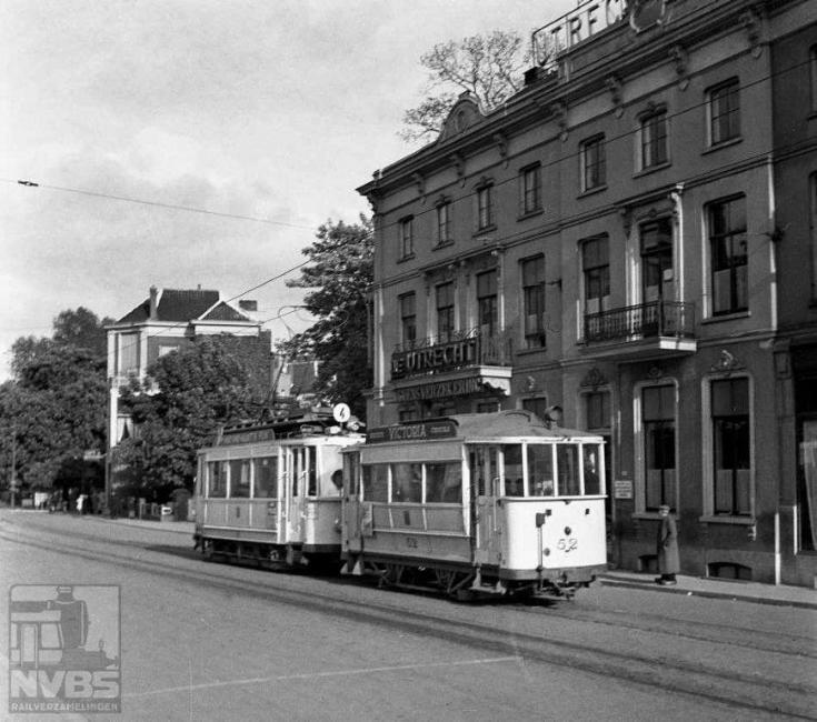 Bij het Arnhemse spoorstation, om precies te zijn in de Utrechtse straat, zien we een tramstel van lijn 4. Op deze lijn rijden niet de nieuwste vierassige motorwagens maar oudere uit de begintijd. Motorwagen 16 dateert uit 1912 en is op dit moment, 22 mei 1944, dus al 32 jaar oud. Maar in de oorlog moest alles wat rijden kon dit ook doen. Aanhanger 52 is nog veel ouder en afkomstig van de Arnhemsche Tramweg Maatschappij, de voorloper van de Gemeentelijke Electrische Tram Arnhem (GETA). Deze exploiteerde vanaf 1880 paardentramlijnen in Arnhem en Velp en de 52 is uit de begintijd van déze maatschappij. Door hevige gevechtshandelingen moest het trambedrijf op 17 september 1944 worden stilgelegd. Er was te veel verwoest aan materieel en infrastructuur om de dienst na de oorlog te hervatten. Gelukkig rijden er nog altijd trolleybussen.Foto: J.A.Bonthuis (129.054C)
