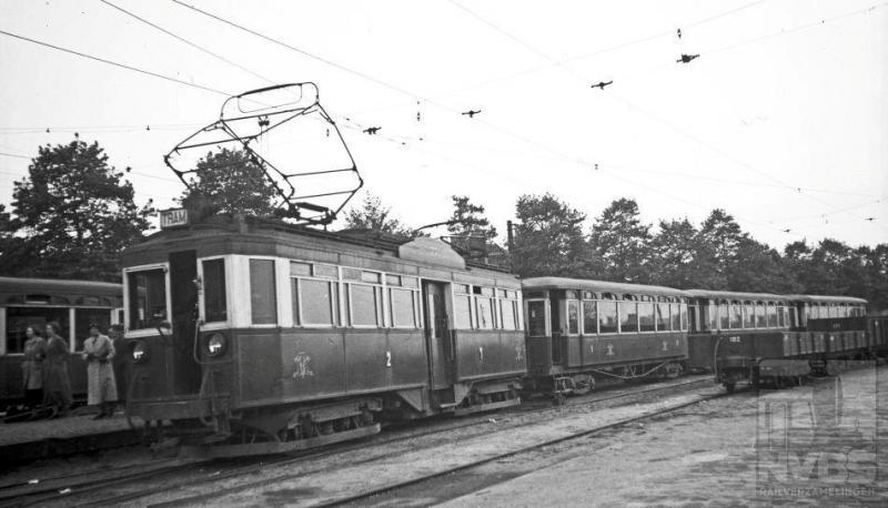 Een lange tram van een motorwagen (77) met drie aanhangwagens van de Nederlandsche Buurtspoorweg Maatschappij (NBM) is aangekomen op het tramstation van Amersfoort vanwaar het NS-station in een paar minuten is te bereiken. Bewoners van de streek tussen Zeist en Amersfoort konden sinds de elektrificatie van deze lijn in 1924 veel sneller het station bereiken. De 77 is van een serie van veertien door Werkspoor speciaal voor deze smalspoorlijn gebouwde vierassige motorwagens. Het rijtuig heeft zijn laatste jaren nog dienst gedaan bij de GETA. De NBM bestreek een groot gebied tussen Utrecht en Arnhem. Plaatsen als Zeist, Doorn, Amersfoort en Rhenen werden bediend.Foto: H.G. Hesselink (170.736A)