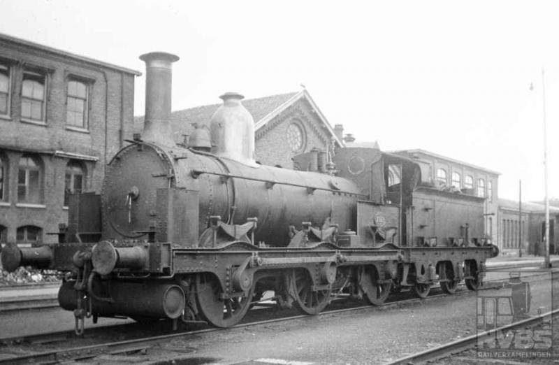 Driemaster-locomotief 2921 werd op 1 juli 1937 door de heer Bonthuis op het terrein van de Wpc Tilburg gefotografeerd. De bijnaam dankt de loc aan de drie gekoppelde assen waarmee zij is uitgerust. Gebouwd in Engeland bij Beyer Peacock & Co, werd zij in 1875 bij de Staatsspoorwegen in dienst gesteld. Na 62 jaar trouwe dienst kan er wel eens wat mankeren natuurlijk (509.005C).