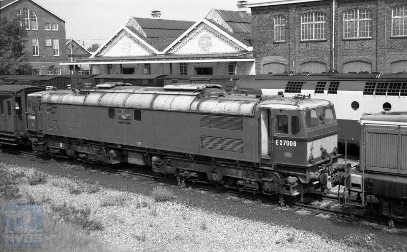In 1970 kocht NS tweedehands van British Rail een zevental elektrische locomotieven, waarvan er zes bij NS in dienst kwamen, de 1501-1506. De bijzonder fraaie machines waren in 1954 gebouwd door Vickers, en hadden dienst gedaan op het traject Manchester-Sheffield dat net als bij NS voorzien was van 1500V gelijkstroom op de bovenleiding. Op de foto zien we de BR 27006 op het terrein van de Wpc Tilburg staan, om getransformeerd te worden tot NS-locomotief 1504. 31 juli 1970. Achter de 27006 kunnen we nog de bovenkant zien van het motorrijtuig van een TEE-treinstel (J.A.Bonthuis; 639.672C).