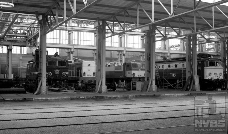 Tot slot nog een plaatje uit Tilburg, waar we in een van de hallen de elektrische locomotieven 1154, 1505 en 1113 plus diesellocomotief 2904 zien staan. Deze laatste was afkomstig van de Staatsmijnen, in de vijftiger jaren door Henschel gebouwd. De serie 2901-2905 heeft maar vijf jaar bij NS dienst gedaan, tot 1975. Hun derde leven gingen zij leiden in Spanje. 17 april 1974 (J.A.Bonthuis; 509.693C).