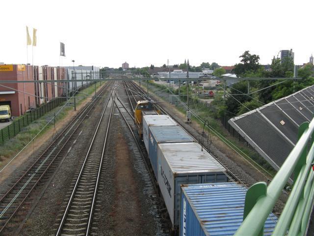 Een containertrein nadert over linkerspoor station Roermond en zal spoedig naar het rechterspoor overlopen.Foto genomen vanaf het viaduct in de Venlose weg.