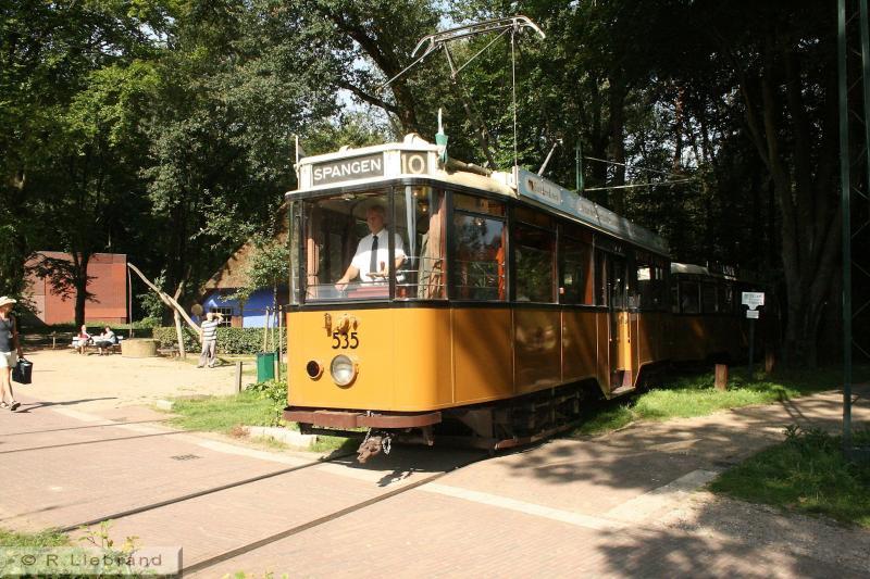 """RET 535, 30 augustus 2008 In 1929 stelde de Rotterdamse Elektrische Tram (RET) de serie 401-459 in dienst. Moderne vierassige trams, in de kleuren zwart en okergeel, gebouwd bij Allan in Rotterdam, Talbot in Aken en Werkspoor in Utrecht. In 1931 volgde de serie 471-570 van hetzelfde type. """"Deze trams golden als een van de modernste in het vooroorlogse Europa,"""" weet Wikipedia te melden. In 1969 werden de laatste exemplaren buiten dienst gesteld. Twintig wagens zijn nog behouden gebleven, waarvan er drie nu in Arnhem rijden. Ze zijn ingericht in de stijl van de jaren dertig. Tram 535 werd in 1931 bij Werkspoor gebouwd. Hij ging in Rotterdam buiten dienst in 1969 en kwam in 1996 naar Arnhem. Aan het begin van dit millennium kreeg het een aanrijding, die een flinke revisie noodzakelijk maakte. Sinds april 2006 is het stel weer rijvaardig. NOM heeft de 535 in bruikleen van de RET."""