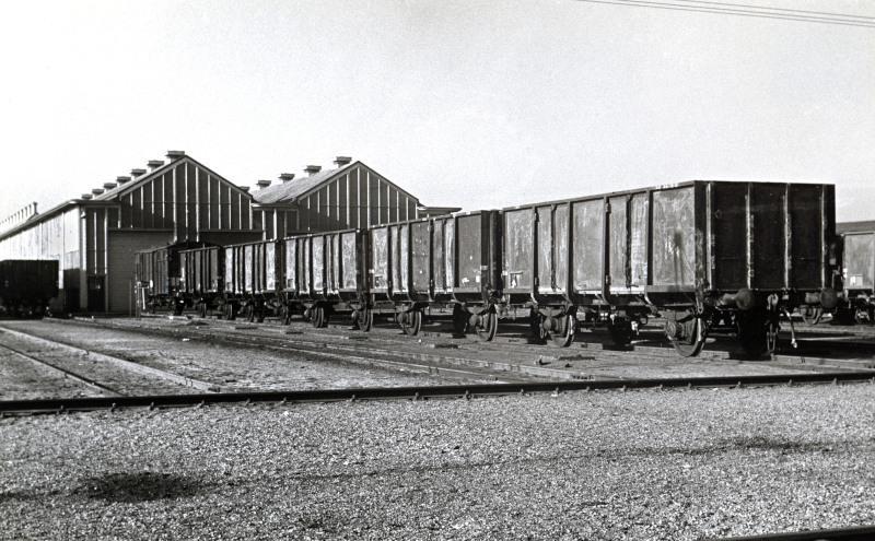 Een rij kolenwagens staat te wachten. Aan dit type wagens had men veel werk omdat ze niet zachtzinnig werden behandeld. Kolenwagens waren nog volop in gebruik voor he transport van de Limburgse kolenmijnen naar de rest vanhet land. Waarschijnlijk is de foto genomen in Blerick waar een dependance van Amersfoort was, en waar veel kolenwagens werden opgeknapt.