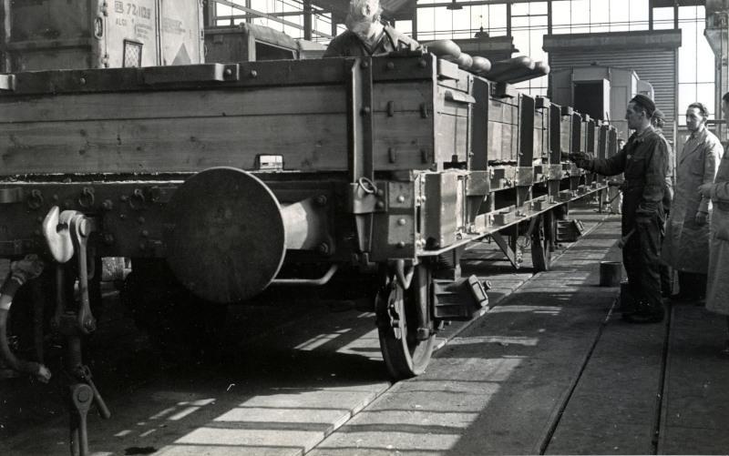 Zandwagens zijn in de grondverf gezet. Deze zandwagens werden door NS zelf gebruikt voor het vervoer van zand vanf de zandwinplaats in Maarn naar werken elders in het land. Ze werden in de werkplaats Amersfoort verbouwd uit andere goederenwagens.