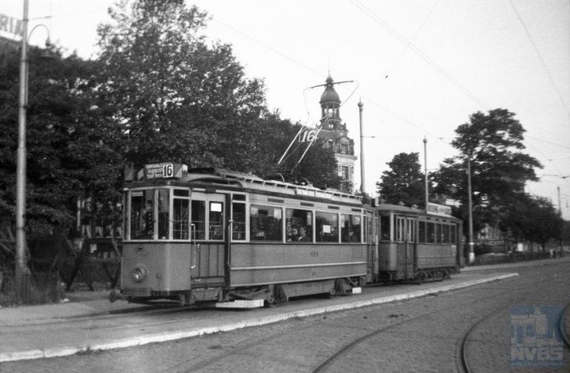Zonder enig vlagvertoon of versiering reed vanaf 18 juni in Amsterdam lijn 16 weer. We zien hier motorwagen 405 met aanhangwagen 790 op de Prins Hendrikkade op deze eerste dag. De tweeassers zouden nog geruime tijd dienst blijven doen in de hoofdstad, tot in de vijftiger jaren. In 1948 kwamen de drieassers en pas in 1957 de eerste vierassers -van Beijnes- op de rails. (foto L.J.A.M. Heijmeijer 131.001; 18-6-1945)