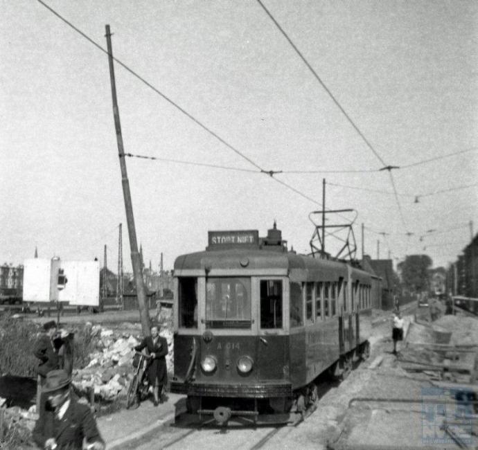In augustus 1945 kon je ook  weer met de NZH-tram van Den Haag naar Leiden reizen. De foto laat duidelijk zien dat de omgeving van de tram nog niet genormaliseerd is. Er was slechts enkelspoor en veel ruimte voor wandelaars en fietsers bleef er niet over als de tram er door moest. Naast de A614-613, een van de fraaie harmonicatrams die het Haarlemse Beijnes in 1932 had geleverd, zien we een diepe bomkrater: hier was een V2-raket ingeslagen na een mislukte lancering. (foto 130.328; 8-8-1945)