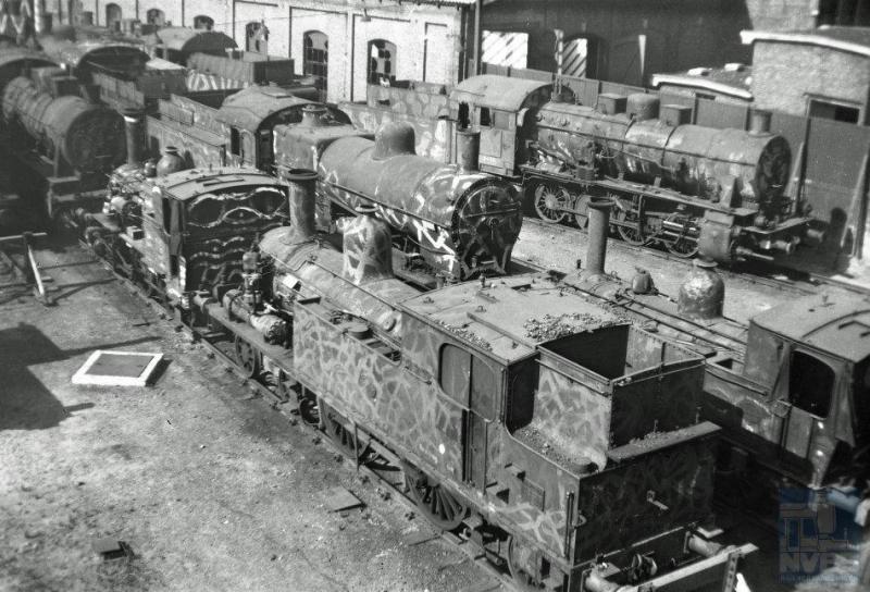 Zondag 17 september 1944 had de regering in Londen het bevel tot de spoorwegstaking gegeven waar op de meeste plaatsen in Nederland gehoor aan werd gegeven. De stoomlocomotieven die er nog waren, met camouflagebeschildering, werden bij de stations gestald zoals op deze foto naast de locloods van station Den Haag Staatsspoor. We zien locomotieven van de series 5500, 7700 en 3700. Op de achtergrond  een G8-locomotief, een van de latere serie 4101-4149.  (foto 509.025; 13-5-1945)