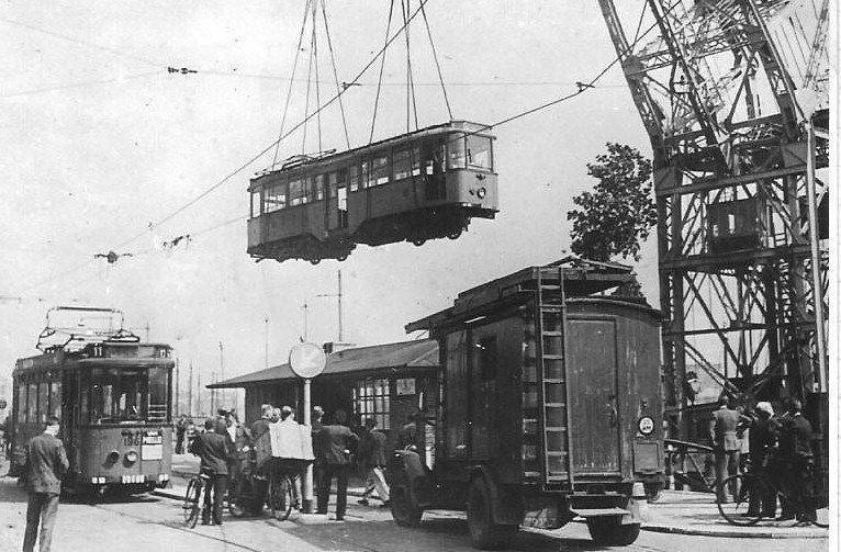 Door de nazi's gevorderde  tramrijtuigen kwamen grotendeels weer naar Nederland terug: in Rotterdam gebeurde dit ook per schip. Met een kraan worden de trams uit het ruim getild en op de rails in de stad gezet. Motorwagen 196 staat er al en vierasser 450 bungelt nog in de lucht maar zal weldra de 196 vergezellen. Beide rijtuigen kwamen na een opknapbeurt weer in de normale dienst. (onbekende fotograaf; 23-5-1945)
