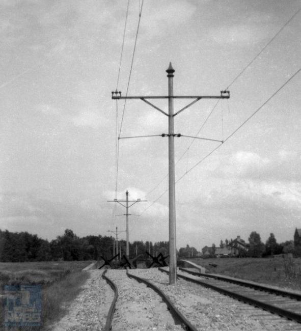 Ook de trambedrijven hebben veel te lijden gehad van de oorlog. Bij de HTM lijn I² naar Leiden hebben mensen in de Hongerwinter op sommige plaatsen de dwarsliggers gesloopt om op te stoken, zoals hier bij de halte Laboratoria in Leiden.  Maar ook al zouden die er nog wel liggen, de tankversperring in de vorm van 'egels' iets verderop had doorrijden sowieso verhinderd. (foto 109.802; 14 juni 1945)