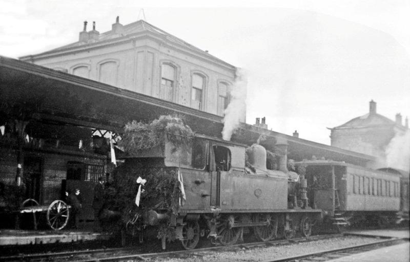 Toch nog een versierde trein te bespeuren, en wel op station Zutphen. De gelegenheid is de eerste trein na het beëindigen van de oorlog naar Winterswijk. Locomotief NS 5504 staat voor een aantal verschillende rijtuigen, waarvan alleen het eerste op de foto is te zien. (foto 509.234; 17-12-1945)