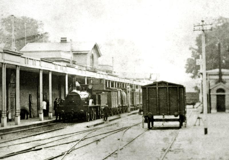 De enige foto uit de tijd dat de HSM (Hollandsche IJzeren Spoorweg-Maatschappij) nog op breedspoor reed. Afgebeeld is het station van Haarlem, ca 1865. De loc is de HOLLAND (gebouwd bij R. Stephenson in 1856).