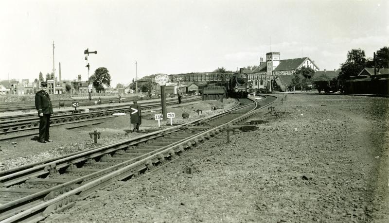 """Op deze foto kijken we in omgekeerde richting vanaf het station van Amersfoort naar het oosten. Deze foto is gemaakt in 1940. We zien in het midden het bord """"Sintels Stortplaats II"""". Hier werd de as uit de stoomlocomotieven gestort; even verderop staat loc 3725 kolen te laden. Langs het spoor zijn de trekdraden te zien waarmee vanuit een seinhuis de wissels en armseinen werden bediend.De loopbrug in de verte en de Phoenix brouwerij zijn allang verdwenen, maar vlak naast het eerder genoemde bord is nog net het eerste station van Amersfoort te zien (het witte gebouw); dit gebouw staat er nog steeds."""