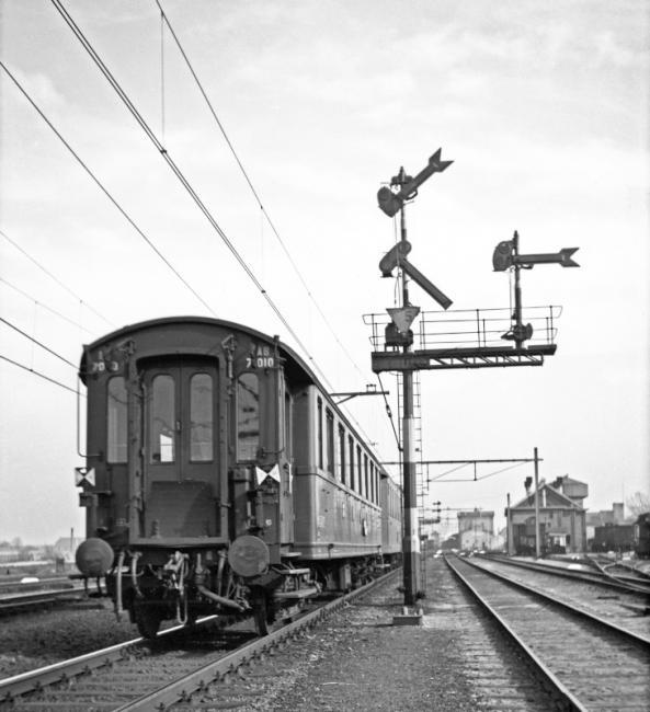 Het inrijsein van station Gouda vanuit de richting Moordrecht met een passerende NS reizigerstrein met achteraan personenrijtuig AB 7010, een D-treinrijtuig, dus vermoedelijk betreft het een internationale trein uit Den Haag SS of Hoek van Holland.Gelet op de uitvoering van de seinarmen en de gebruikte schaarstellers dateert het sein uit de periode 1932-1937. De trein heeft de gebruikelijke sluitseinborden; aan de aanwezigheid van de sluitseinen kon men zien dat de trein compleet was.
