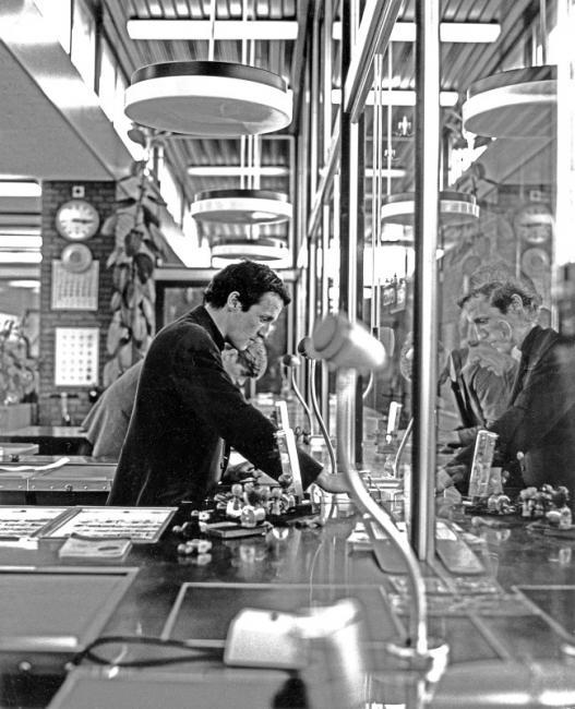 Een moderner plaatskaartenkantoor, ook te Amsterdam. De lokettist heeft aan zijn rechterhand de kasten waar de kaartjes klaarliggen; het apparaat dat omhoog steekt gebruikt hij om op de kaartjes van een datumstempel te voorzien. Daarnaast heeft hij nog diverse andere stempels tot zijn beschikking.
