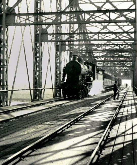 Spoorbrug in Rhenen, loc serie 3500 (ex NBDS) met sneltrein. De foto dateert uit 1936.De brug was onderdeel van de verbinding van Amsterdam naar Duitsland via Amersfoort, Nijmegen en Kleef, door de HSM ingesteld als concurrent voor de verbinding via Arnhem.De brug is in de 2e wereldoorlog vernield en na de oorlog niet meer hersteld.