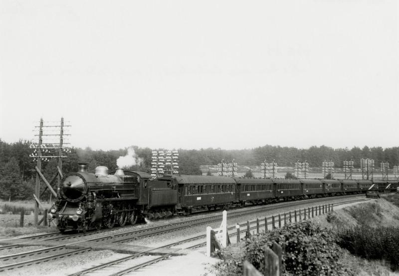 """Trein met stoomloc uit de serie 3600 (dit type stond bekend als """"Zeppelin"""") onderweg te Oosterbeek-Laag. De trein is de Nederland Expres, die te Marseille aansluiting gaf op de boot naar Indië, waardoor die reis vanuit Nederland met enkele dagen werd bekort. De wagons zijn van Wagons-Lits (CIWL, of Compagnie Internationale des Wagons-Lits et des Grands Express Europeens).Langs de lijn zijn de telegraafdraden te zien die nodig waren voor de communicatie tussen de stations. Overal langs de hoofdspoorlijnen zag men dergelijke telegraafpalen, alleen meestal niet met zoveel draden eraan als in dit geval."""