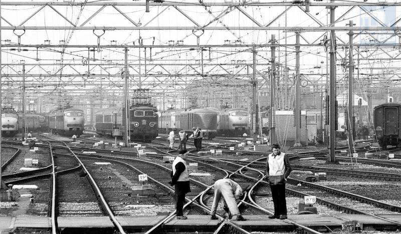 """Op het Westelijk Eiland Amsterdam CS wordt aan een half Engels wissel gewerkt. Van links naar rechts: eentreinstel mat ′54 (Hondekop), een treinstel mat ′64 (Plan T of V), een nog blauwe eloc serie 1100 in oorspronkelijke uitvoering met een TEE naar Duitsland, een postrijtuig voor treinstellen een zogenaamde """"Pec"""" (Postrijtuig voor elektrische tractie met wc), nog een treinstel mat′64 en een eloc serie 1100 in geel/grijs met botsneus.De foto is gemaakt door Frans Boom op 14 februari 1977."""