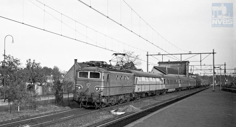 """""""Exprestrein"""" 38 (Amsterdam-Maastricht), bestaande uit elektrische locomotief NS 1111, een bagagewagen type DV, rijtuigen plan D en een CIWL restauratierijtuig tijdens de passage van Boxtel.Boze tongen beweren dat de kleur turquoise van dit materieel vooral was gekozen op aandringen van de echtgenote van NS-directeur F.Q. den Hollander, en dat de onderhoudswerkplaatsen er een hekel aan hadden omdat deze kleur heel moeilijk constant te houden was.Datum: 24 mei 1951"""
