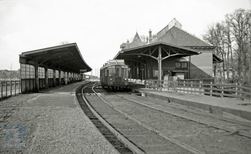 Gezicht op benzinemotorrijtuig NS omBC 1905 naast het perron van het uit 1911 daterende station Kampen. Links op de foto is de brug over de IJssel zichtbaar, die het station met de stad verbindt. Het motorrijtuig behoort tot de door Werkspoor gebouwde serie omBC 1904-1910 met DWK motor, in 1929 in dienst gesteld voor de Woldjerspoorweg tussen Groningen en Delfzijl. Het rijtuig sleet na de oorlog zijn laatste jaren rond Zwolle en zal in 1951 worden afgevoerd, maar pas in 1969 gesloopt, nadat het eerst nog als noodwoning heeft gediend.De perronkap links is er niet meer, en er rijden nu moderne treinen, maar verder is er aan het station niet veel veranderd.