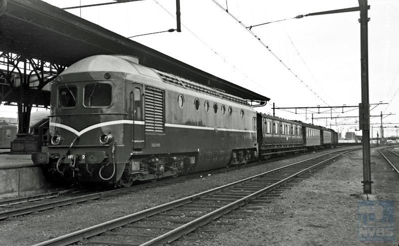 Diesellocomotief NS 2601 met een reizigerstrein uit Venlo langs het perron van station Eindhoven. Dit locomotieftype stond bekend als ′Beelen′ vanwege hun gelijkenis met het (kale) hoofd van de heer L.J.M. Beel, minister-president in 1946-1948 en 1958-1959. De locs zijn gebouwd door Werkspoor; vanwege veelvuldig optredende defecten werden de locs al na vijf jaar buiten dienst gesteld.Achter de loc een rijtuig serie B 6400.